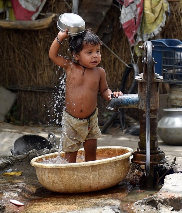 A young Indian child pours water on himself as he trie to cool himself off in New Delhi on May 28, 2015. More than 1,100 people have died in a blistering heatwave sweeping India, authorities said, as forecasters warned searing temperatures would continue. AFP PHOTO/MONEY SHARMA.        (Photo credit should read MONEY SHARMA/AFP/Getty Images)